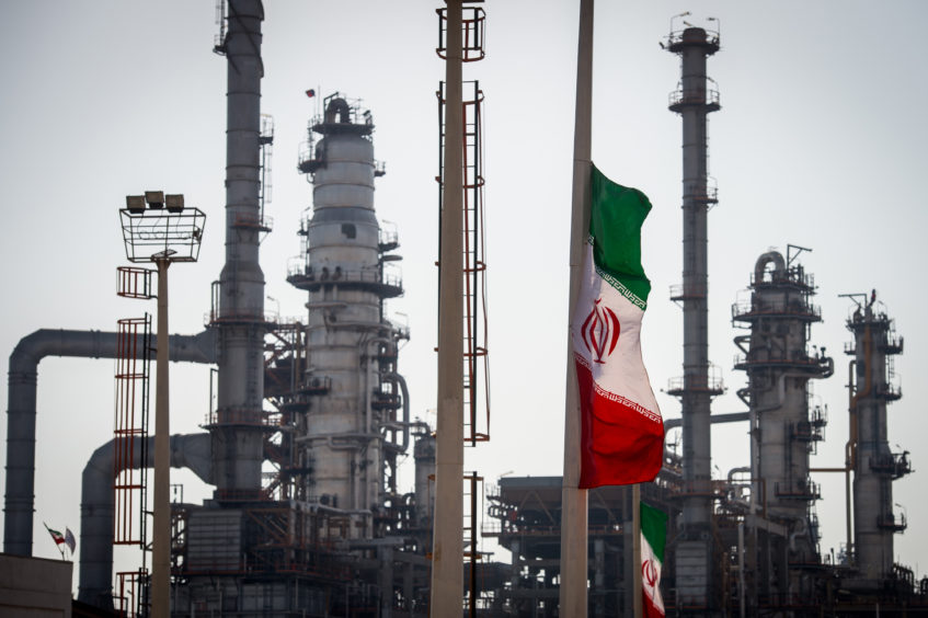 An Iranian national flag flies near gas condensate processing facilities in the new Phase 3 facility at the Persian Gulf Star Co. (PGSPC) refinery in Bandar Abbas, Iran, on Wednesday, Jan. 9. 2019. The third phase of the refinery begins operations next week and will add 12-15 million liters a day of gasoline output capacity to the plant, Deputy Oil Minister Alireza Sadeghabadi told reporters. Photographer: Ali Mohammadi/Bloomberg