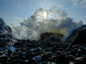 Crashing wave against a rock with the sunshine behind