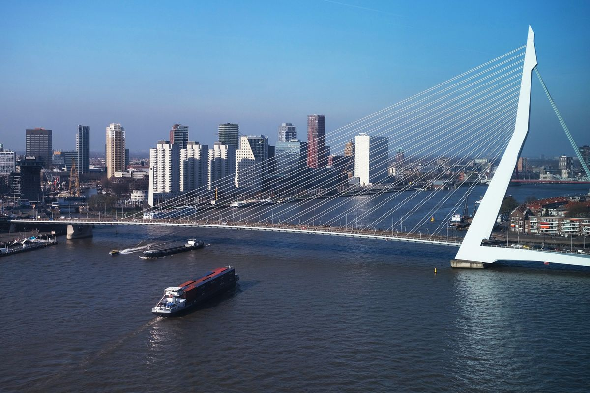 A ship goes under a bridge with a city scape behind