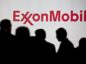 Attendees stand near Exxon Mobil Corp. signage during the World Gas Conference in Washington, D.C., U.S, on Tuesday, June 26, 2018.  Photographer: Andrew Harrer/Bloomberg