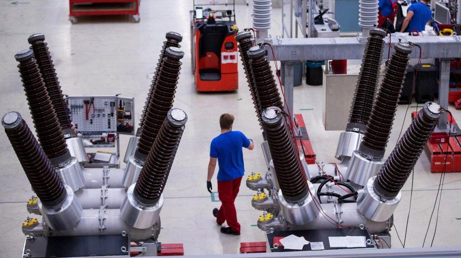 An employee stands near dead tank circuit breakers inside Siemens AG switchgear electronic power unit factory in Berlin, Germany, on Thursday, Sept. 13, 2018.