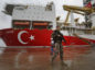 A Turkish police officer patrols the dock, backdropped by the drilling ship 'Yavuz' scheduled to be dispatched to the Mediterranean, at the port of Dilovasi, outside Istanbul, Thursday, June 20, 2019. Turkish officials say the drillship Yavuz will be dispatched to an area off Cyprus to drill for gas. Another drillship, the Fatih, is now drilling off Cyprus' west coast at a distance of approximately 40 miles in waters where the east Mediterranean island nation has exclusive economic rights. The Cyprus government says Turkey's actions contravene international law and violate Cypriot sovereign rights. (AP Photo/Lefteris Pitarakis)
