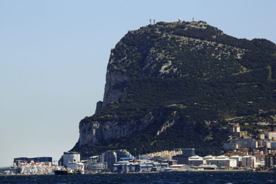 Commercial and residential buildings stand along the waterline at the base of the rock of Gibraltar in Gibraltar, U.K., on Sunday, March 6, 2016.  Photographer: Luke MacGregor/Bloomberg