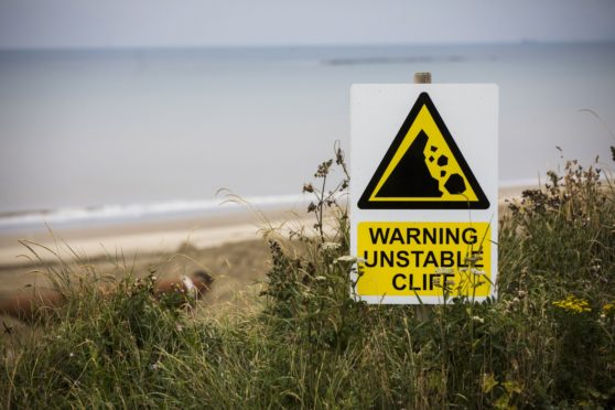 A sign stands at the cliff edge during an operation by Royal HaskoningDHV to protect against erosion of the cliffs bordering the Bacton Gas Terminal