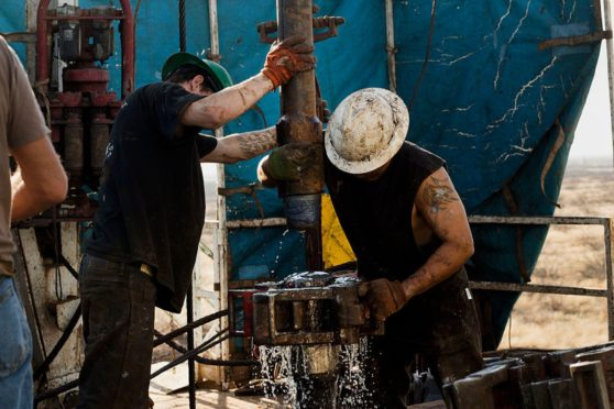 Workers on Big Dog Drilling Rig 22, owned by Endeavor Energy Resources, L.P., on the outskirts of Midland, Texas, connect drill bits and drill collars used to extract natural petroleum on Friday, December 12, 2014. (Brittany Sowacke/Bloomberg)