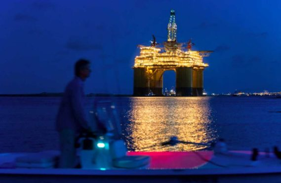A boater passes the Royal Dutch Shell Plc Olympus tension leg platform (TLP) at dawn as it sets sail from Kiewit Offshore Services in Ingleside, Texas, U.S., on Saturday, July 13, 2013. Olympus, Shell's biggest constructed tension leg platform, started the ten day, 425-mile voyage to Mars B Field in the Gulf of Mexico on July 13. Photographer: Eddie Seal/Bloomberg