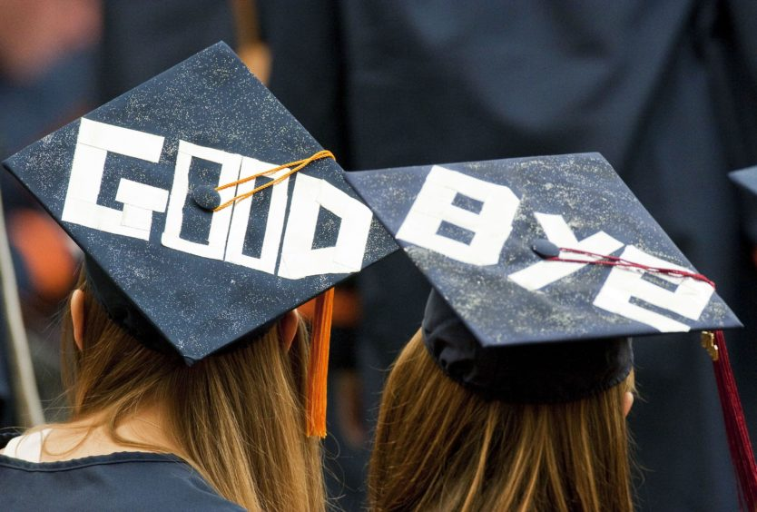 """Two graduates display a farewell message on their mortarboards during Syracuse University's commencement ceremony at the Carrier Dome in Syracuse, New York, U.S., on Sunday, May 16, 2010. Students entering one of the weakest job markets in history need to have the courage to speak the truth, """"even when it's unpopular,"""" JPMorgan Chase & Co. Chief Executive Officer Jamie Dimon told graduates. Photographer: Michael Okoniewski/Bloomberg via Getty Images"""