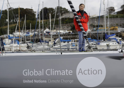 Greta Thunberg poses for a picture on the boat Malizia as it is moored in Plymouth, England Tuesday, Aug. 13, 2019.