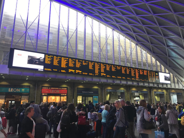 People waiting for trains at King's Cross station, London, after all services in and out of the station were suspended on Friday when a power cut caused major disruption across the country. PA