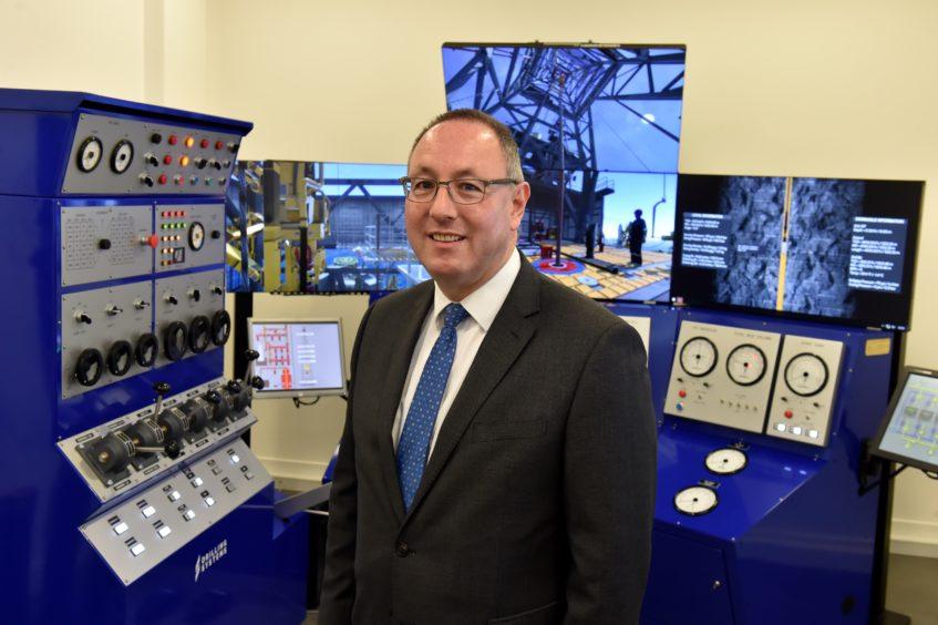 Paul de Leeuw standing in front of RGU's decommissioning simulator.