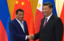 The presidents of China (right) and the Philippines shake hands.