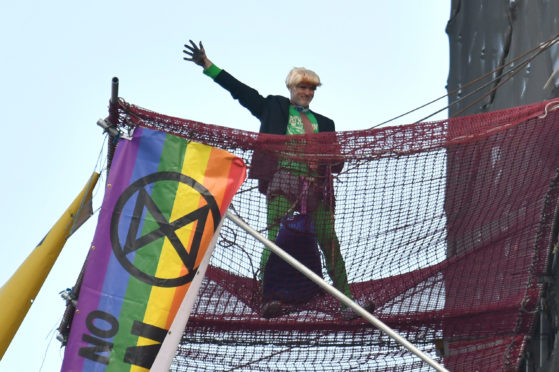 An Extinction Rebellion protester who has scaled the scaffolding surrounding Big Ben at the Houses of Parliament, Westminster, London. PA Photo. Picture date: Friday October 18, 2019. See PA story ENVIRONMENT Protests. Photo credit should read: Dominic Lipinski/PA Wire