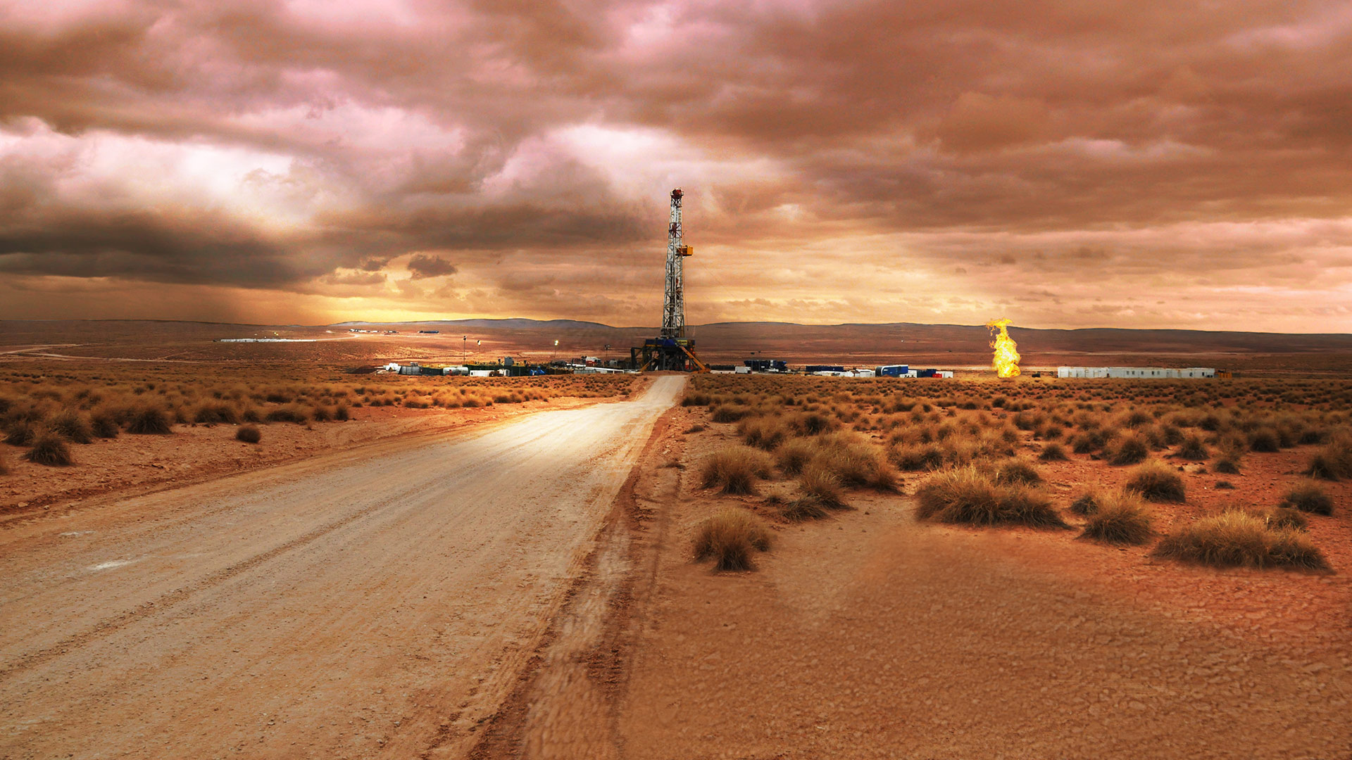 Drilling rig at end of a dusty road, with orange sky