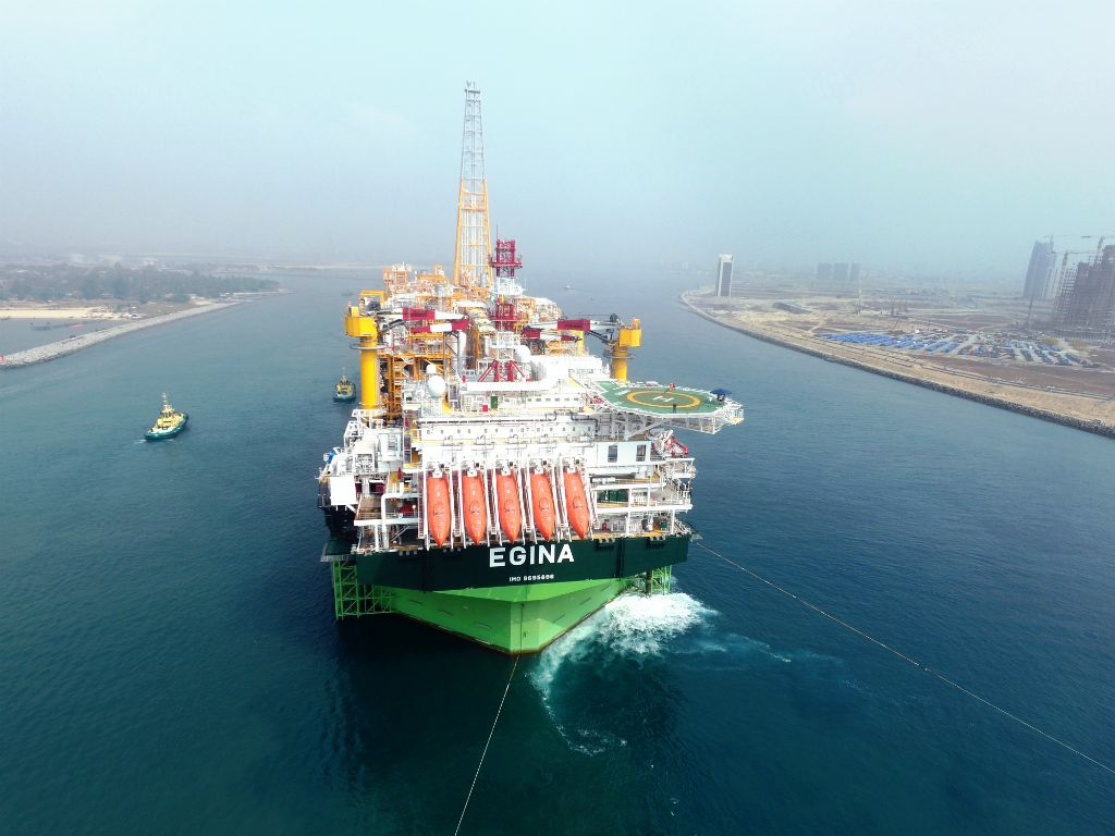 An FPSO with a green hull leaves dock