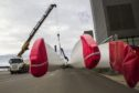 Protective covers sit on wind turbine blades as they are moved at the Vestas Wind Systems A/S blade factory in Lem, Denmark, on Wednesday, Sept. 25, 2013. Photographer: Freya Ingrid Morales/Bloomberg