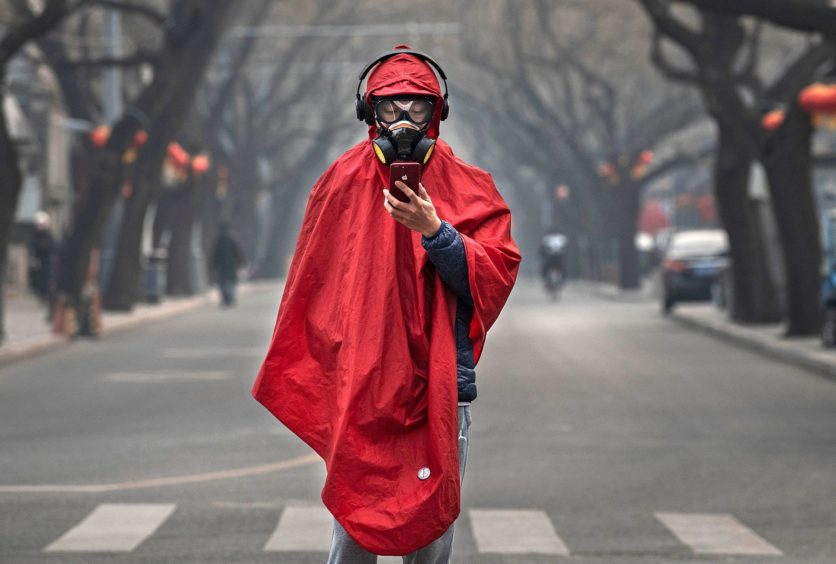 BEIJING, CHINA - JANUARY 26: A Chinese man wears a protective mask, goggles and coat as he stands in a nearly empty street during the Chinese New Year holiday on January 26, 2020 in Beijing, China. The number of cases of a deadly new coronavirus rose to over 2000 in mainland China Sunday as health officials locked down the city of Wuhan earlier in the week in an effort to contain the spread of the pneumonia-like disease.  Photo by Kevin Frayer/Getty Images)