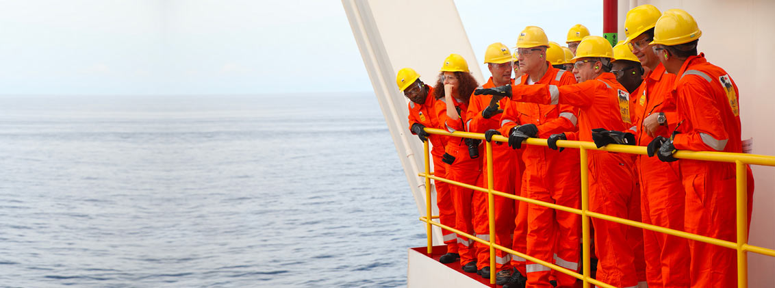 MEn in overalls look out from FPSO into the ocean