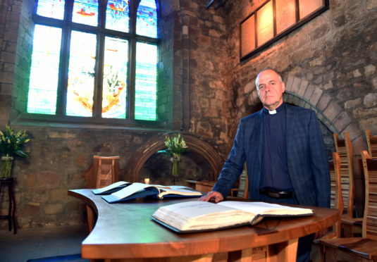 Oil and gas chaplain, Rev Gordon Craig. Normally based in Tullos, he is pictured here with the Book of Remembrance at the Kirk of St Nicholas.