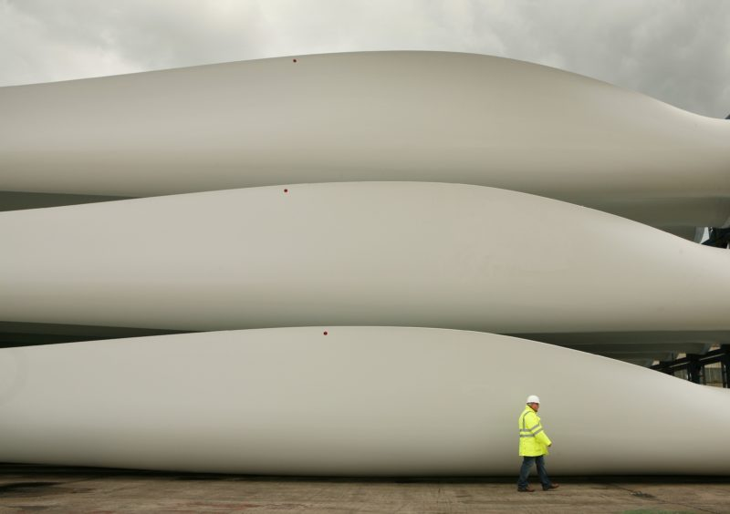 A worker passes stored wind turbine blades at the Harland & Wolff shipyard on August 14, 2008 in Belfast, Northern Ireland.  (Photo by Peter Macdiarmid/Getty Images)
