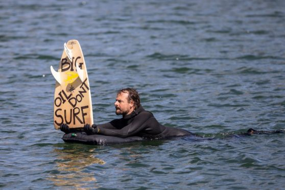 """A man holds up a board reading """"Big oil don't surf"""" during a surf demonstration, a so-called paddle-out, taking place on May 12, 2019 in the harbor pool outside the Opera House in Oslo, Norway. - The surfers demonstrate against a planned oil exploration of Norwegian multinational energy company Equinor in the The Great Australian Bight. (Photo by Ola Vatn / NTB Scanpix / AFP) / Norway OUT        (Photo credit should read OLA VATN/AFP via Getty Images)"""
