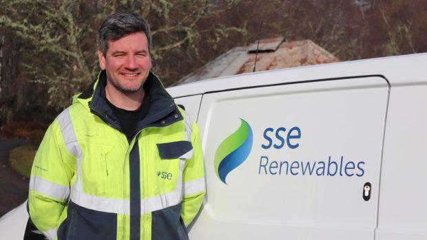 Colin Marr, SSE Renewables Wind Farm Supervisor alongside an SSE Renewables electric vehicle.