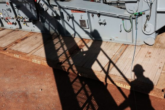The shadows of workers with Apache Corp. are viewed at the Patterson 298 natural gas fueled drilling rig on land in the Permian Basin on February 5, 2015 in Mentone, Texas.