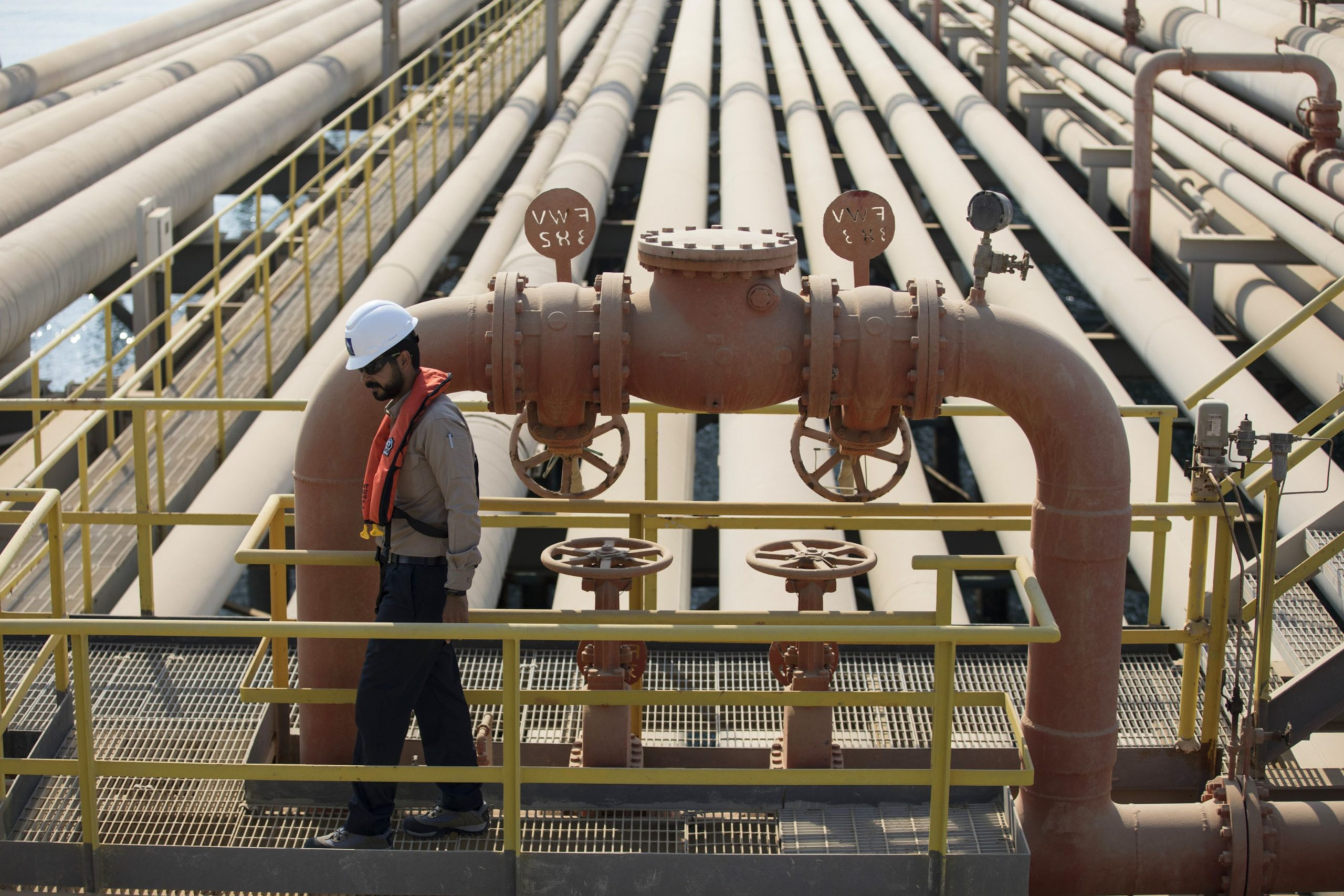 An employee inspects pipes used for landing and unloading crude and refined oil at the North Pier Terminal, operated by Saudi Aramco, in Ras Tanura, Saudi Arabia, on Monday, Oct. 1, 2018.  Photographer: Simon Dawson/Bloomberg