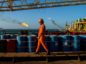 A worker passes stores of oil drums and gas flares while working aboard an offshore oil platform in the Persian Gulf's Salman Oil Field, operated by the National Iranian Offshore Oil Co., near Lavan island, Iran, on Friday, Jan. 6. 2017. Nov. 5 is the day when sweeping U.S. sanctions on Iran's energy and banking sectors go back into effect after Trump's decision in May to walk away from the six-nation deal with Iran that suspended them. Photographer: Ali Mohammadi/Bloomberg