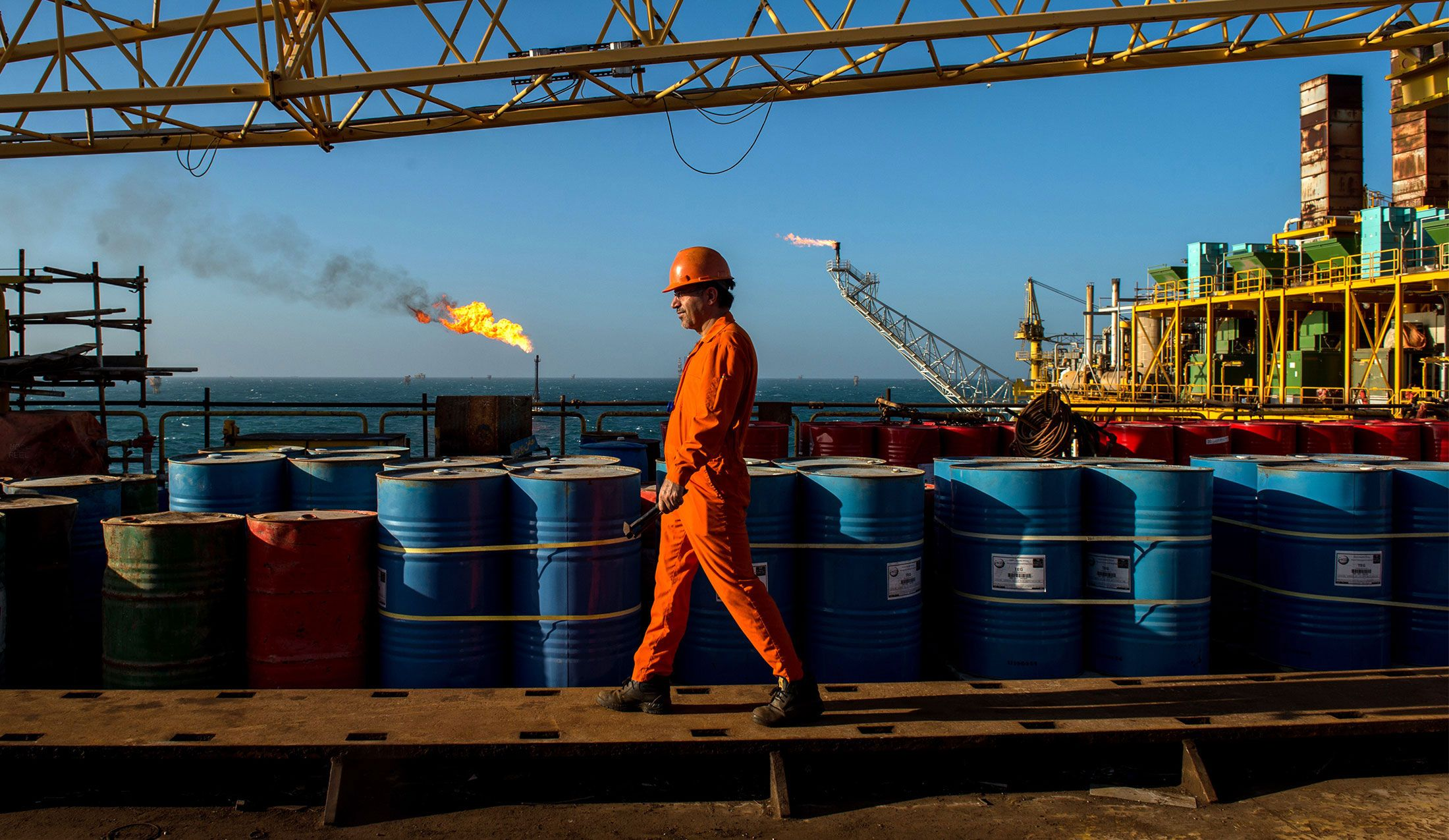 A worker passes stores of oil drums and gas flares while working aboard an offshore oil platform in the Persian Gulf's Salman Oil Field, operated by the National Iranian Offshore Oil Co., near Lavan island, Iran, on Friday, Jan. 6. 2017. Photographer: Ali Mohammadi/Bloomberg