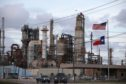 An American and Texas flag stand in front of the Chevron Corp. Pasadena Refinery in Pasadena, Texas, U.S., on Sunday, March 8, 2020. Houston has been purposefully going green for more than a decade. The municipal government gets 92% of all the power it uses in the buildings it owns from wind and solar and has been on the U.S. Environmental Protection Agency's list of the largest renewable power users since 2016. Photographer: Sharon Steinmann/Bloomberg