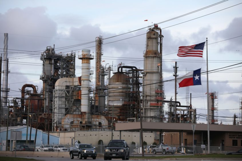 An American and Texas flag stand in front of the Chevron Corp. Pasadena Refinery in Pasadena, Texas, U.S., on Sunday, March 8, 2020.  Photographer: Sharon Steinmann/Bloomberg
