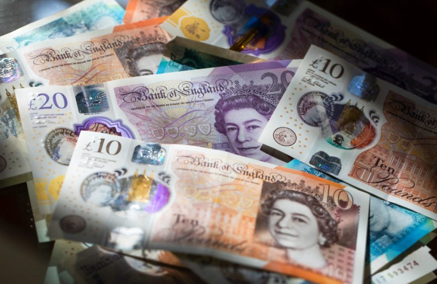 British twenty, ten, and five pound notes sit in this arranged photograph in Danbury, U.K., on Monday, March 23, 2020. The pound rose, boosted by broad dollar weakness, after the U.K. government banned all unnecessary movement of people for at least three weeks in order to reduce the spread of coronavirus. Photographer: Chris Ratcliffe/Bloomberg