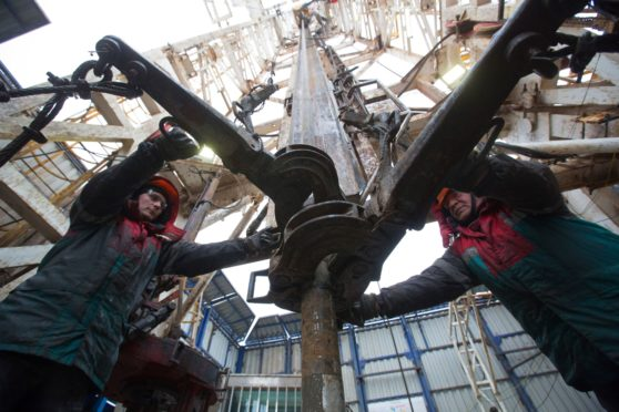 Oil workers connect gear to drilling pipes at the rotary table on a drilling rig, operated by Tatneft PJSC, on an oilfield near Almetyevsk, Tatarstan, Russia, on Tuesday, March 6, 2019. Tatneft explores for, produces, refines, and markets crude oil. Photographer: Andrey Rudakov/Bloomberg
