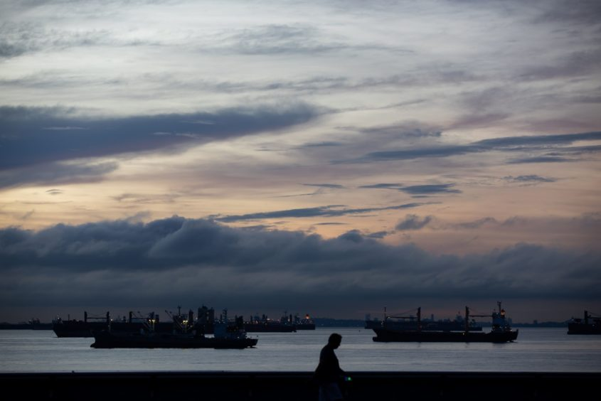 Ships sit moored at sunrise in Singapore.  Photographer: Bloomberg/Bloomberg