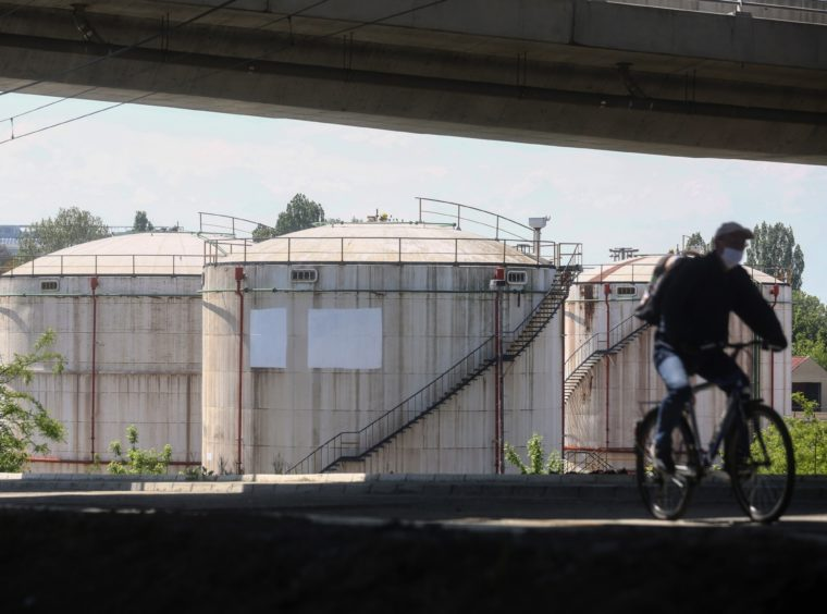 A cyclist wearing a protective face mask rides past oil storage silos at an oil and gas storage facility, operated by Gazprom Neft PJSC, in Belgrade, Serbia, on Tuesday, April 28, 2020. Crude whipsawed near $11 a barrel after a major index tracked by billions of dollars in funds bailed out of near-term contracts for fear prices may turn negative again. Photographer: Oliver Bunic/Bloomberg