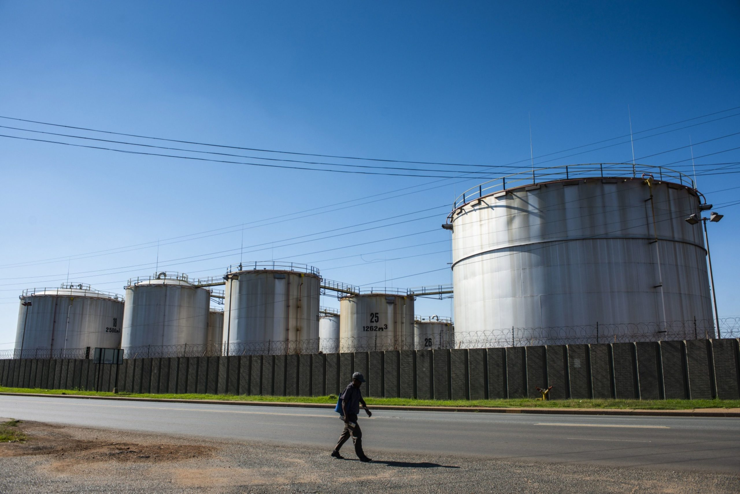 A pedestrian walks alongside oil storage tanks at a facility in the Alrode district
