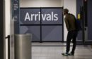 A traveler, wearing a protective face mask, passes through the arrivals area after landing at London Luton Airport in Luton, U.K., on Friday, May 1, 2020. Ryanair Holdings Plc will cut 3,000 jobs and said it will challenge some 30 billion euros ($33 billion) in state aid being doled out to save its European competitors. Photographer: Chris Ratcliffe/Bloomberg
