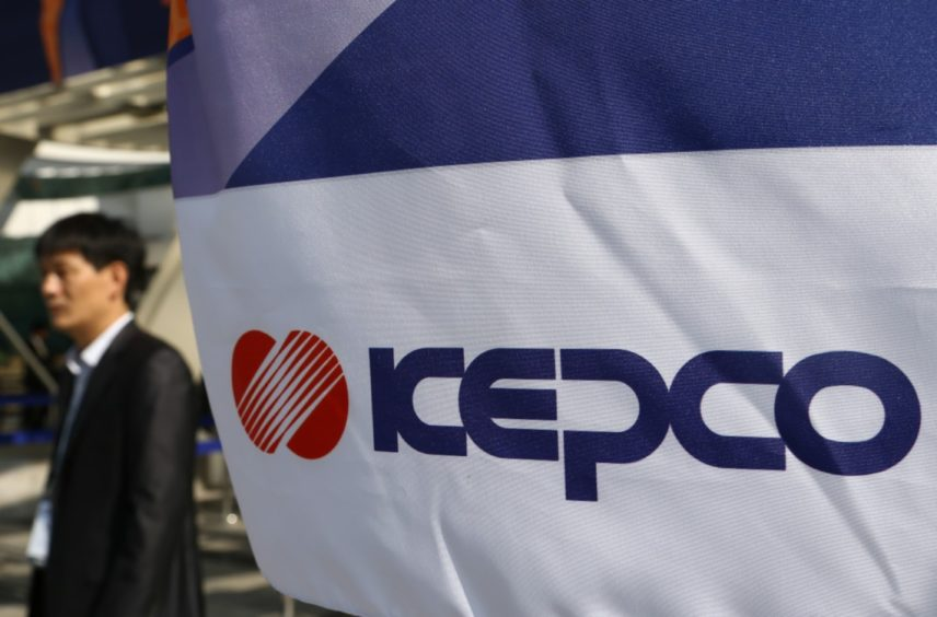 An attendee walks past Korea Electric Power Corp. (Kepco) signage displayed at the 22nd World Energy Congress (WEC) in Daegu, South Korea, on Monday, Oct. 14, 2013.  Photographer: SeongJoon Cho/Bloomberg