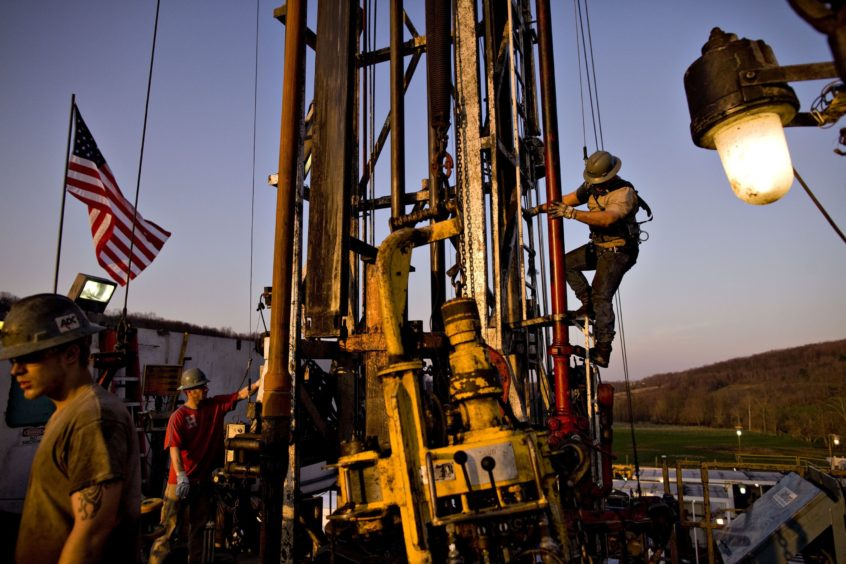Nomac Drilling Corp. derrick man Justin Spruell, right, climbs down from an overhead platform after connecting a section of drill pipe on a Chesapeake Energy Corp. natural gas drill site in Bradford County, Pennsylvania, U.S., on Tuesday, April 6, 2010.  Photographer: Daniel Acker/Bloomberg