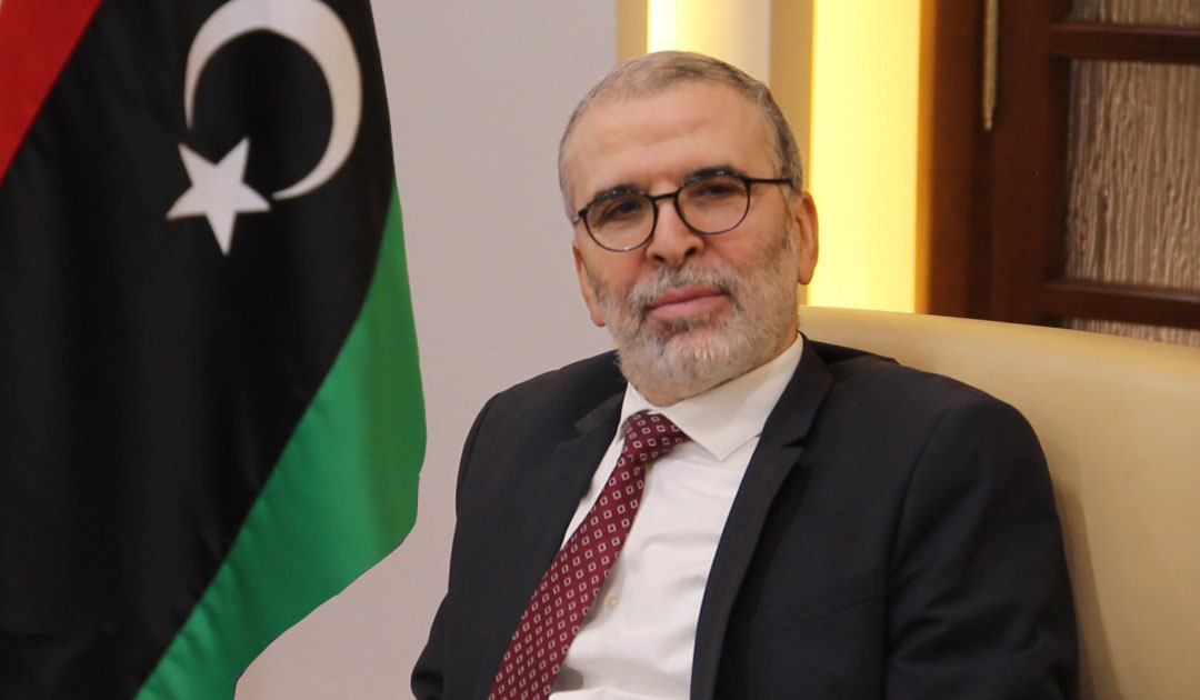 Man with glasses next to part of Libyan flag
