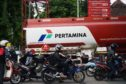 Motorcyclists wait in line in front of a tanker truck at a PT Pertamina gas station in Jakarta, Indonesia, on Wednesday, Jan. 21, 2015. Indonesia will overhaul national oil company Pertamina as the government seeks to improve the management of state-owned enterprises and deliver infrastructure projects after slashing fuel subsidies. Photographer: Dimas Ardian/Bloomberg