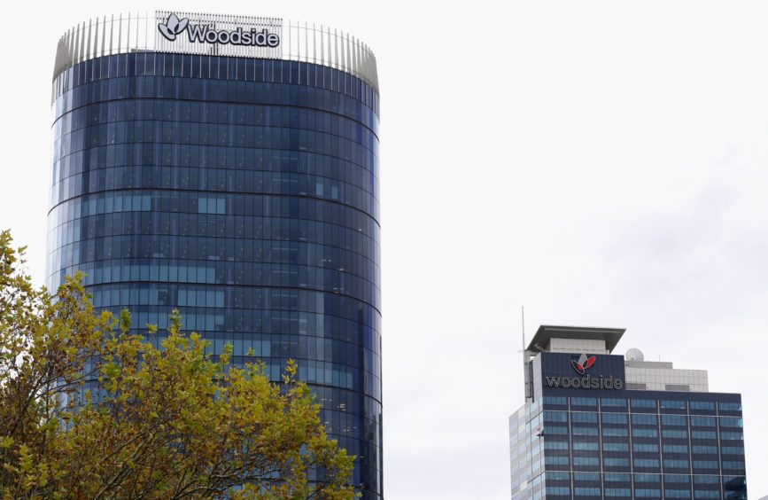 The Woodside Petroleum Ltd. logo is displayed atop the company's new headquarters, left, and Woodside Plaza building in Perth, Australia. Photographer: Sergio Dionisio/Bloomberg
