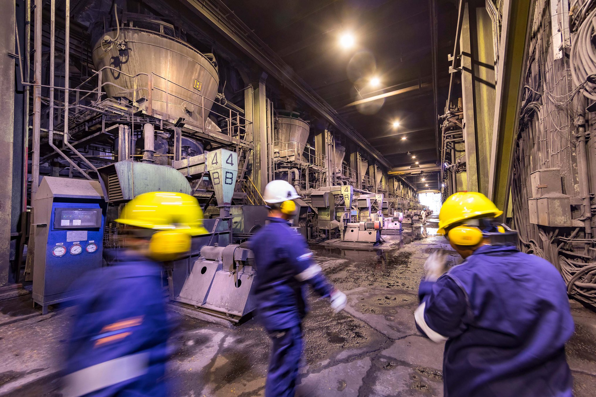 Workers in hard hats in motion through industrial setting