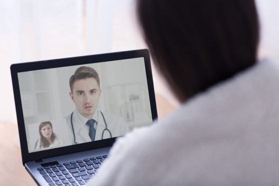 Close-up of a computer screen displaying a video chat between a doctor and a patient