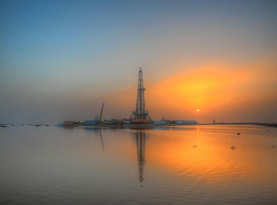 Oil rig against an orange sunset