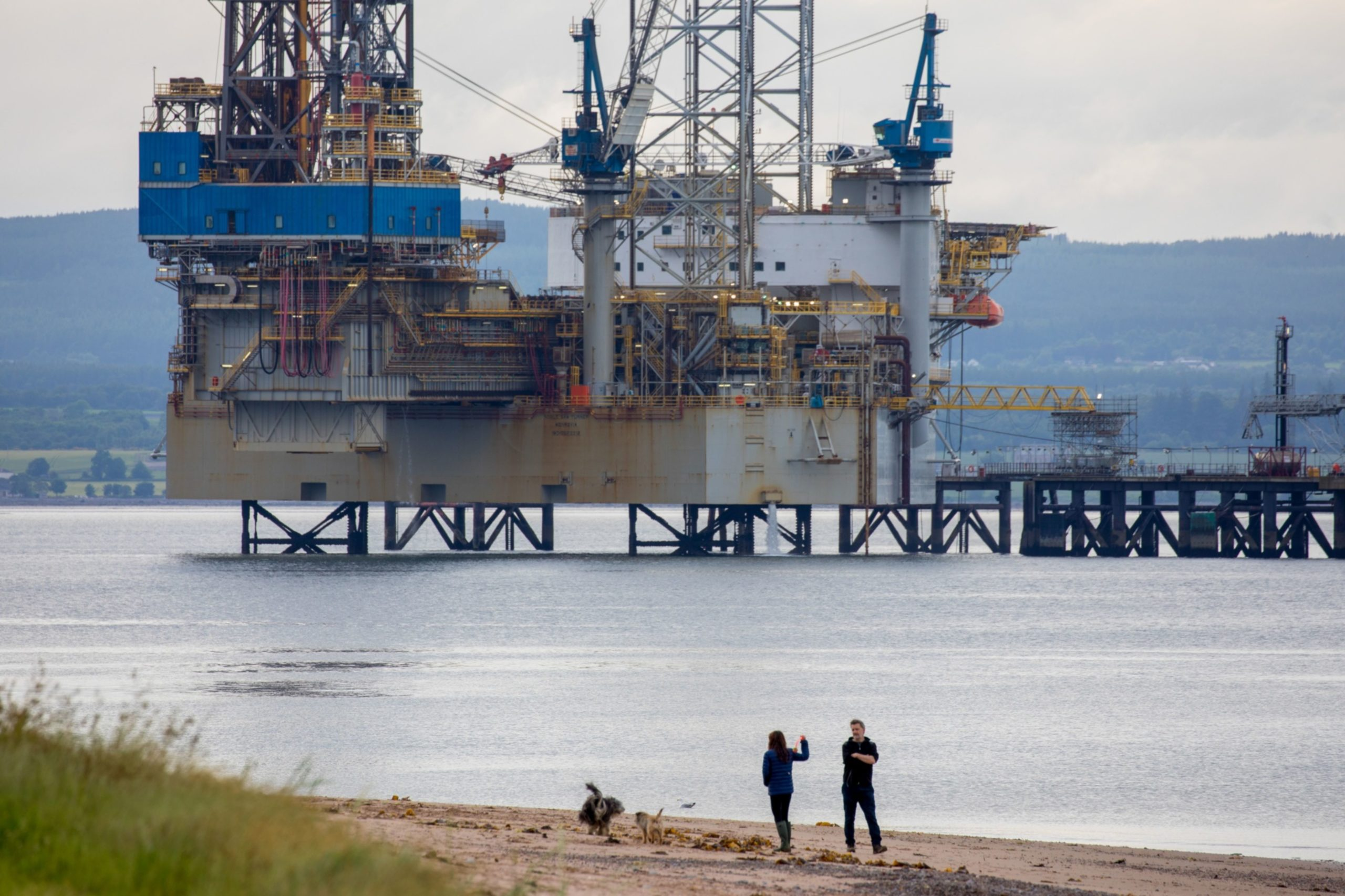 Pedestrians walk along a beach near the Noble Sam Turner jack-up drilling rig, operated by Noble Corp., in Cromarty, U.K. Photographer: Jason Alden/Bloomberg