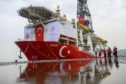 Journalists walk next to a red drilling ship