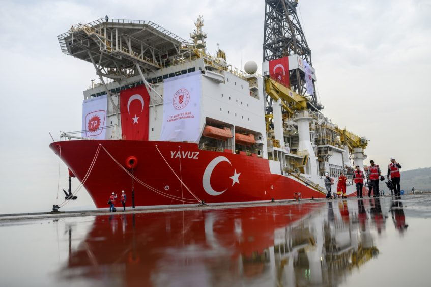 Journalists walk next to the drilling ship 'Yavuz' scheduled to search for oil and gas off Cyprus, at the port of Dilovasi, outside Istanbul, on June 20, 2019. Photographer: Bulent Kilic/AFP/Getty Images