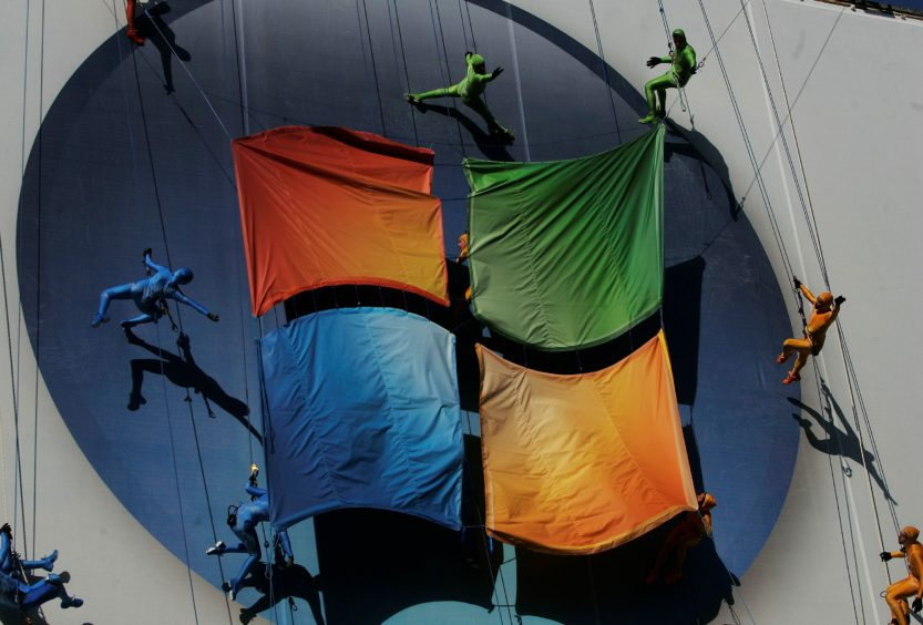 """Members of the """"GROUNDED Aerial Dance Theater"""" hang from ropes and dance on a poster promoting Vista, a new version of Microsoft Windows, on the side of a warehouse building on Manhattan's west side January 29, 2007 in New York. (Photo by Chris Hondros/Getty Images)"""