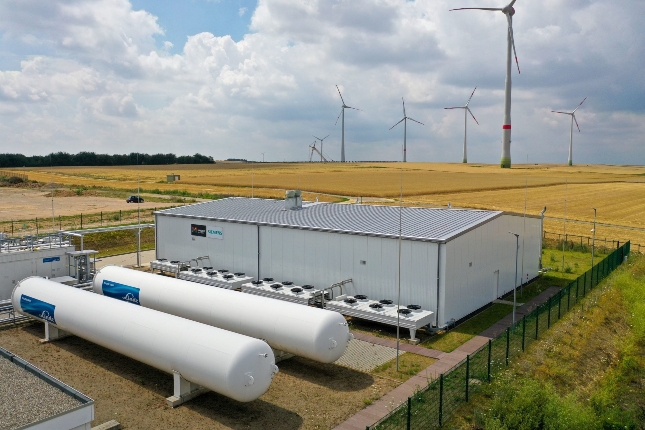 Wind turbines stand in view of the hydrogen electrolysis plant stands.